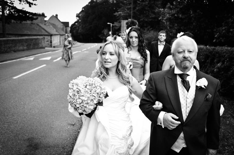 proud father walks bride to church