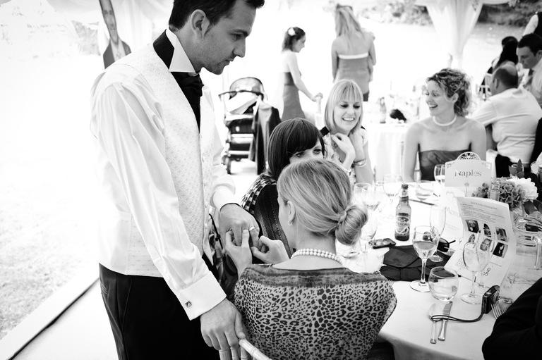 guest admires groom's wedding ring