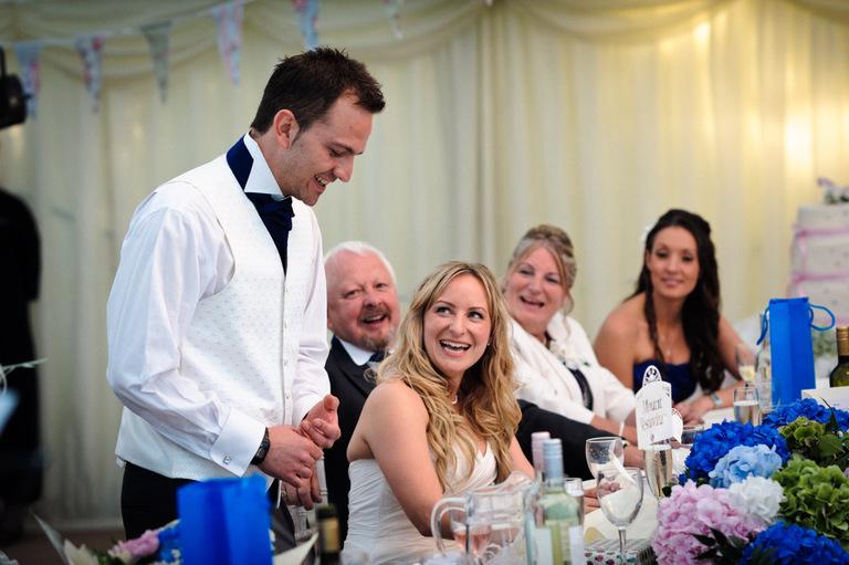 smiling bride during groom speech