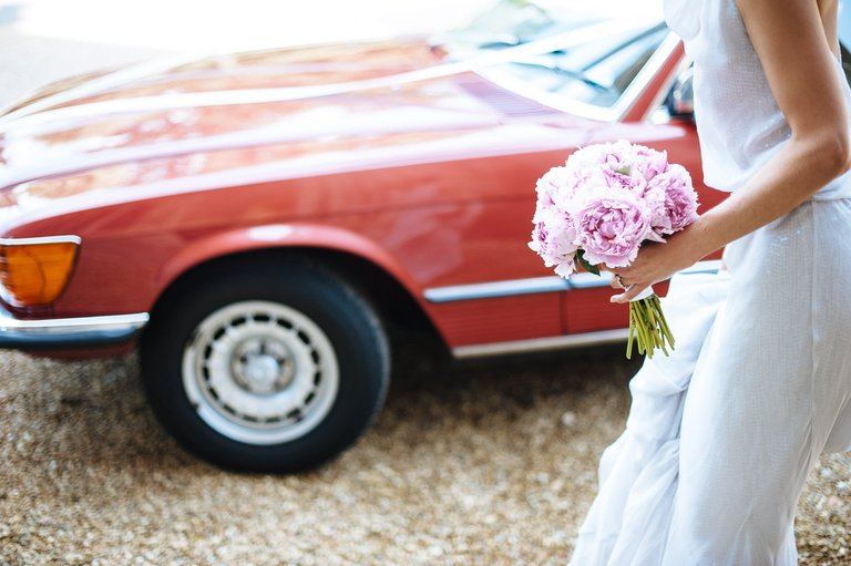 bride flowers and red mercedes convertible