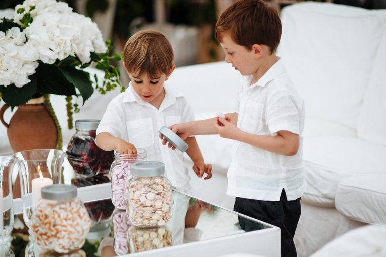 little boys at a wedding stealing sweets