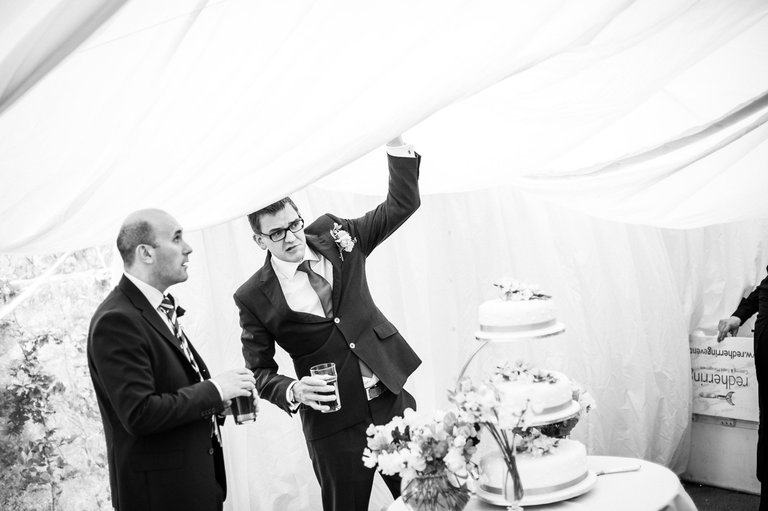 groom holding up the collapsing wedding marquee
