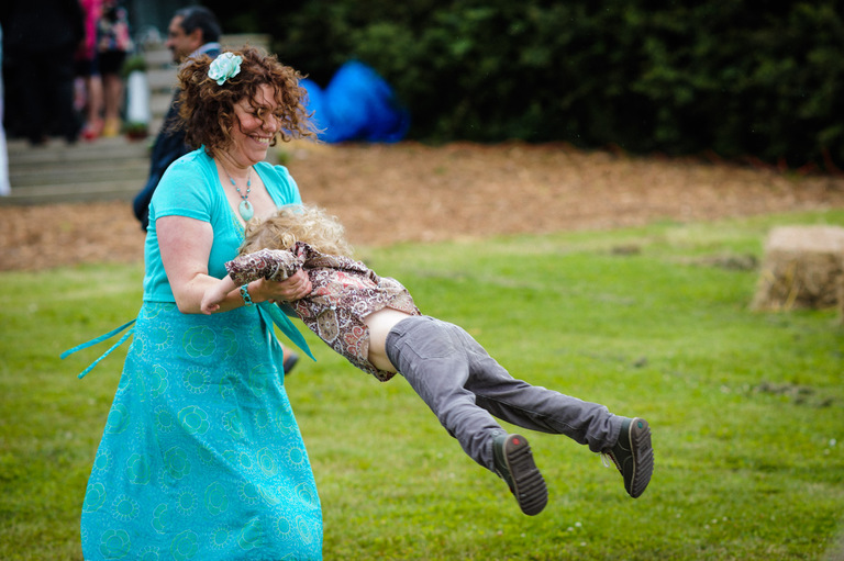 mum swinging her son around at a wedding