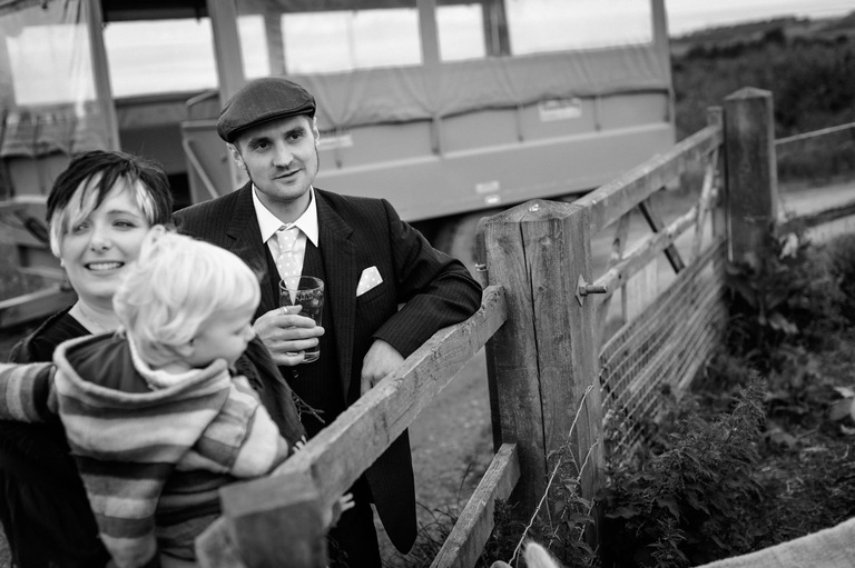 groom wearing flat cap with a pint on a farm