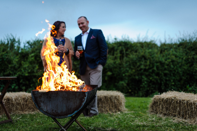 wedding guests standing around a fire pit
