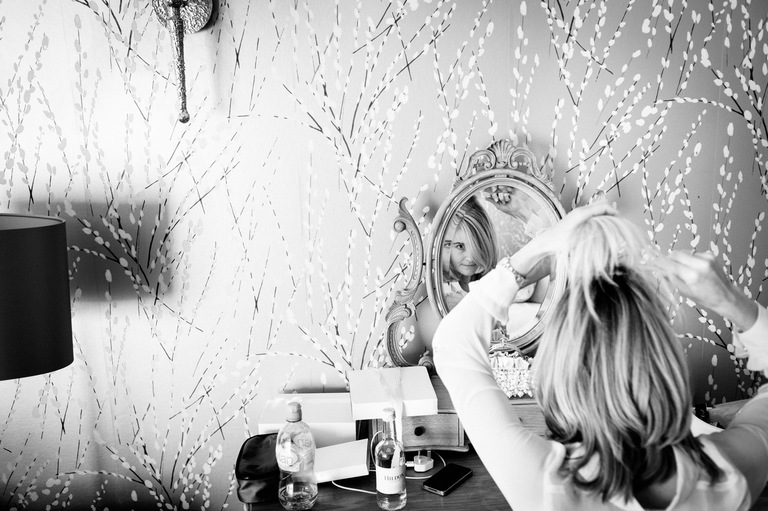 bride fixing her hair in the mirror
