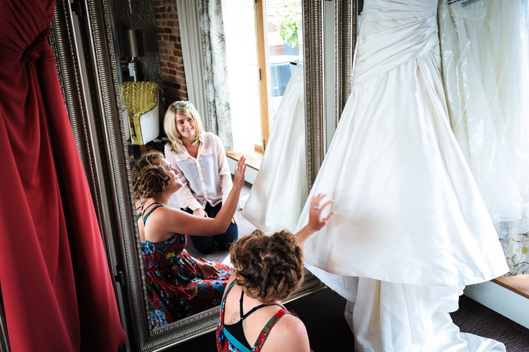 bride and bridesmaid admiring wedding dress