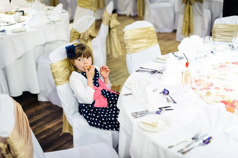 little girl sat alone at a wedding table