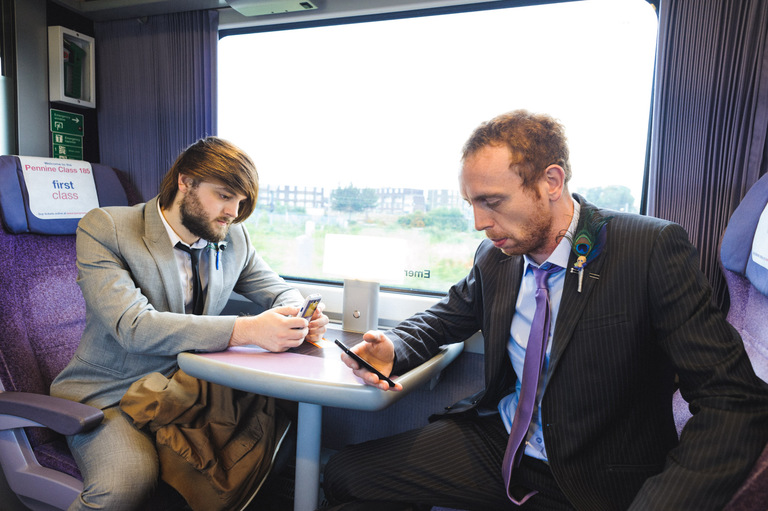 groomsmen texting on a train on the way to a wedding