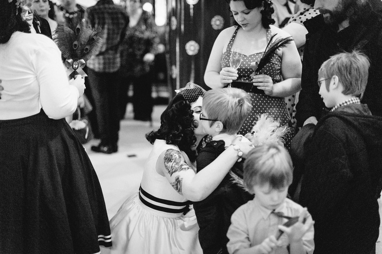 bride giving one of her young guests a kiss