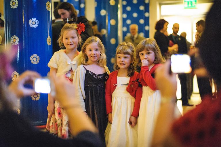 little girls at a wedding having their photo taken
