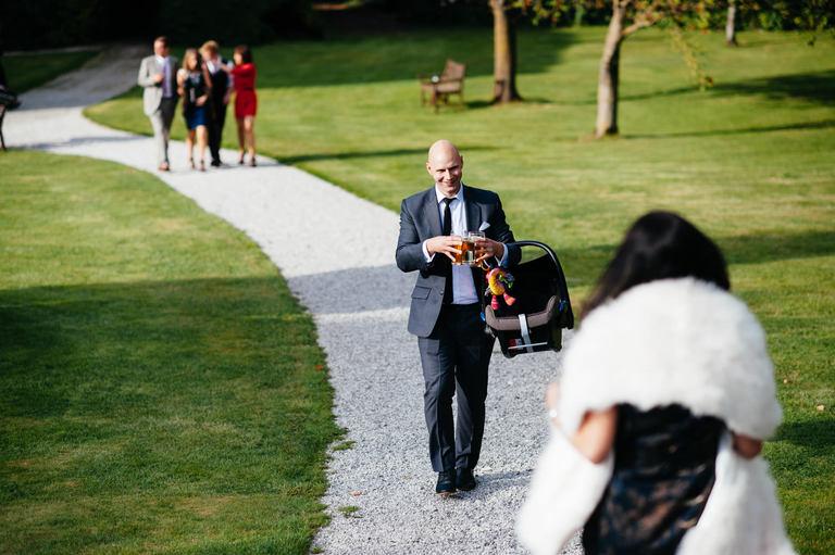 wedding guest carrying 3 beers