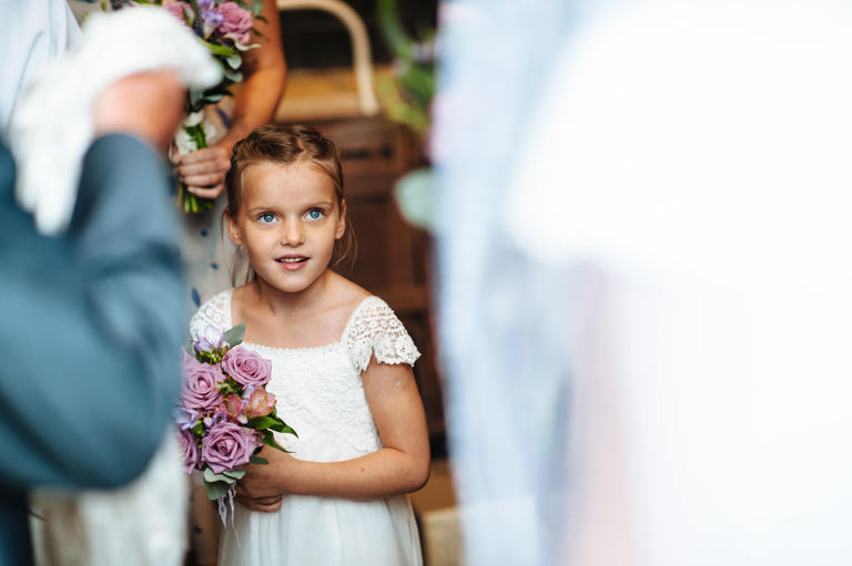 flower girl smiles at bride