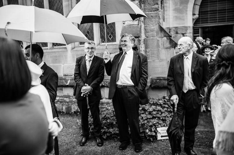 wet wedding guests umbrellas