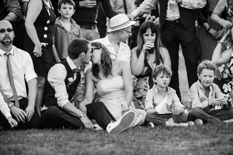 bride groom kissing sat on the grass