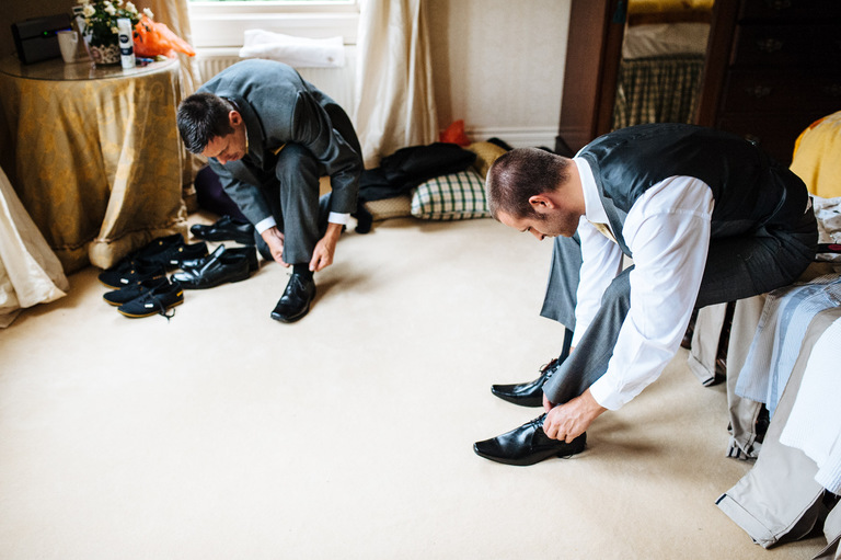 groom best man putting shoes on