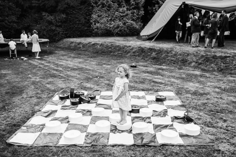 little girl standing on a giant chess set at wedding