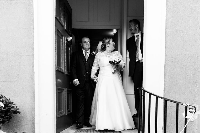 bride and groom surprised as they leave the church