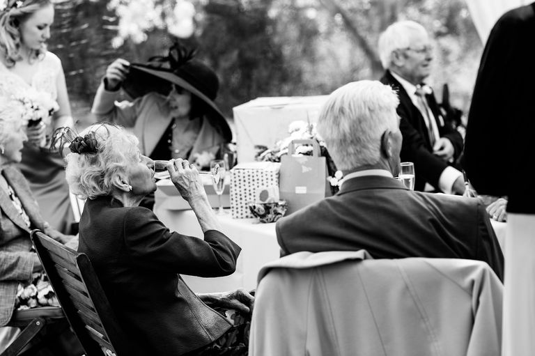 elderly lady drinking wine at a wedding