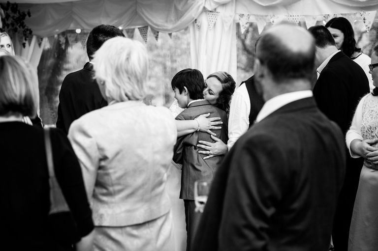 bride hugging a young wedding guest