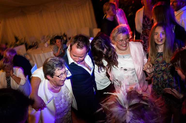 groomsman dancing with ladies wedding reception