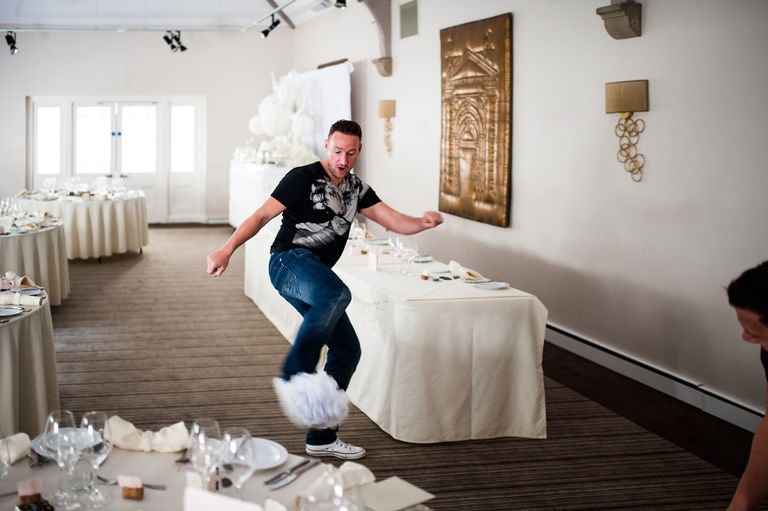 groom playing football with wedding decorations