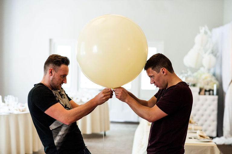 groom and best man tying a wedding balloon