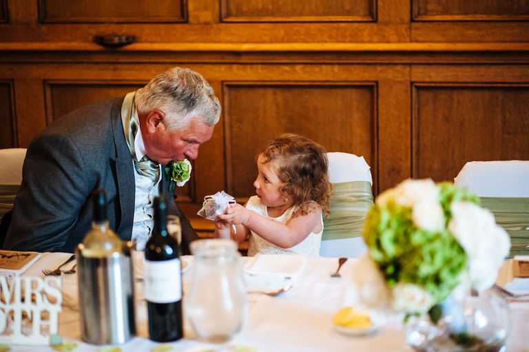 little bridesmaid gives present to father of bride