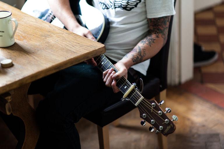 tattooed wedding best man playing guitar