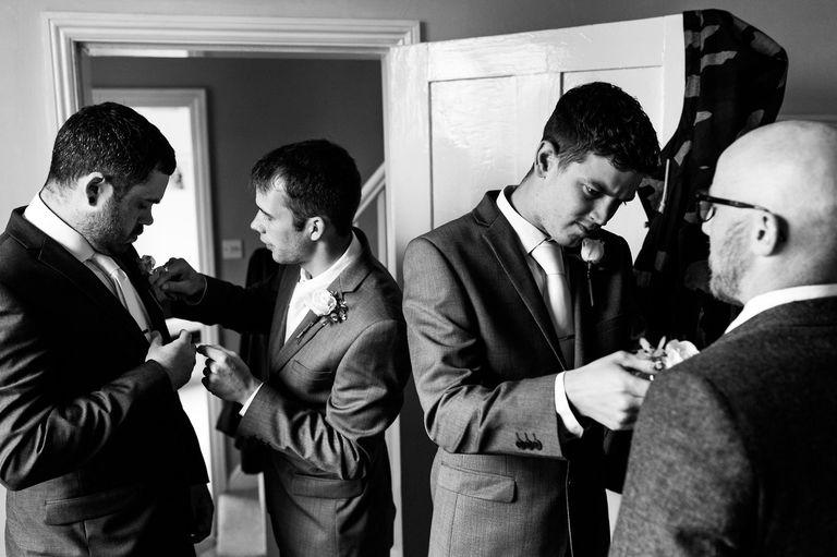 fitting flowers on groomsmen