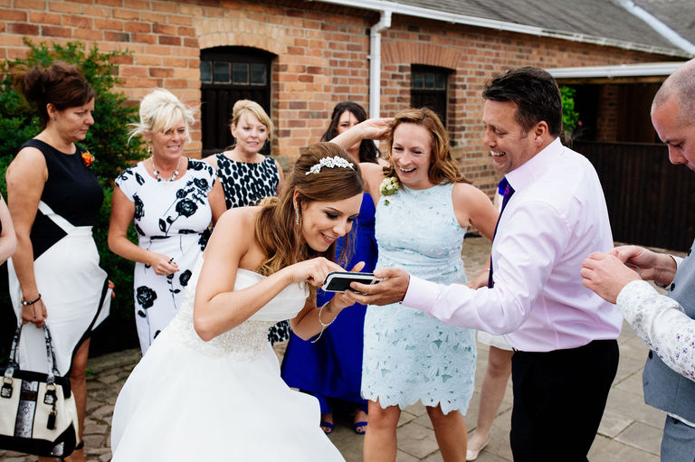 bride looking at photos on phone