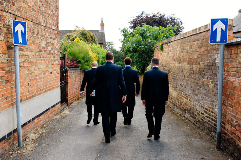 groomsmen walking to wedding one way street