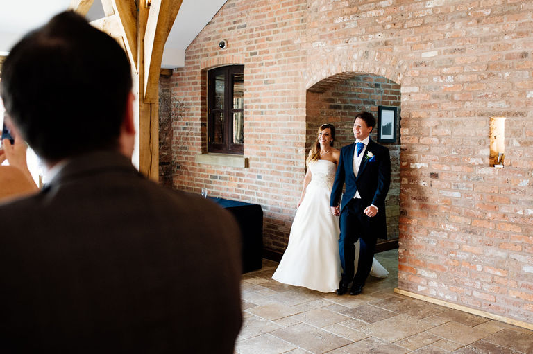 bride and groom enter their wedding breakfast