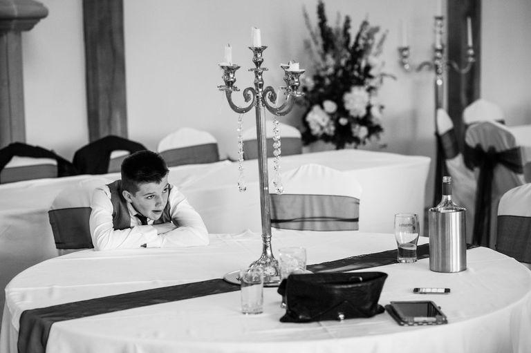 boy looking bored at wedding
