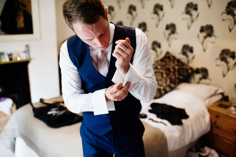 groom putting on cufflinks