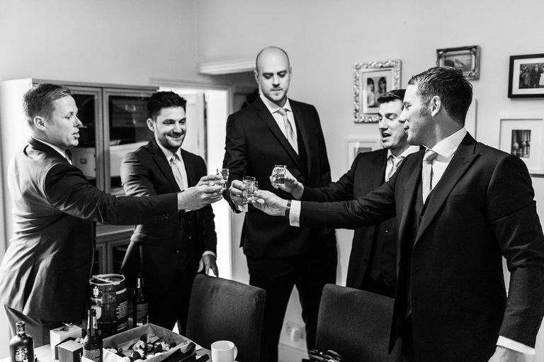 groom and groomsmen having shots before leaving home