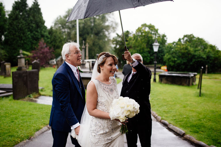 bride arriving at church in the rain