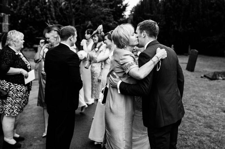 groom receiving a kiss from wedding guest