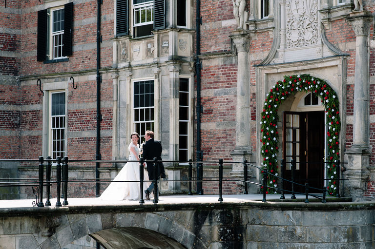 bride and groom walking over a drawbridge