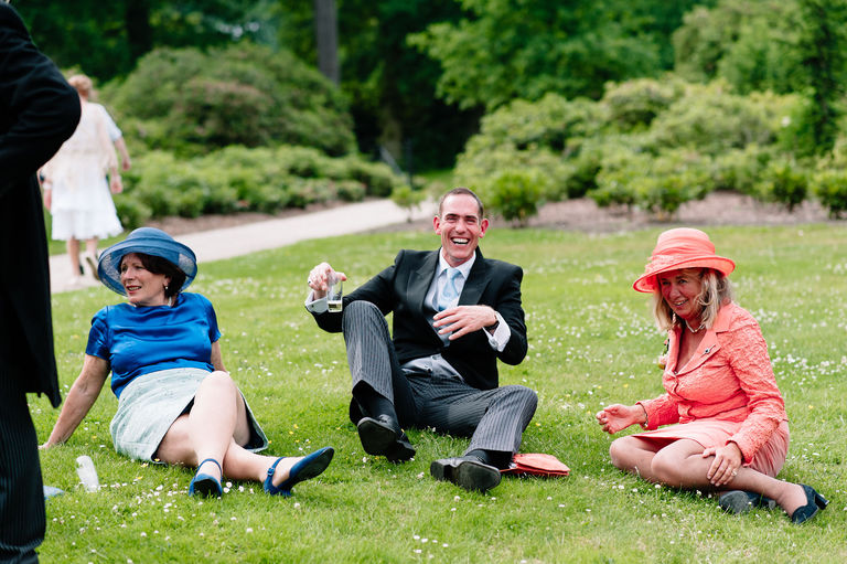 laughing wedding guests sat on the grass