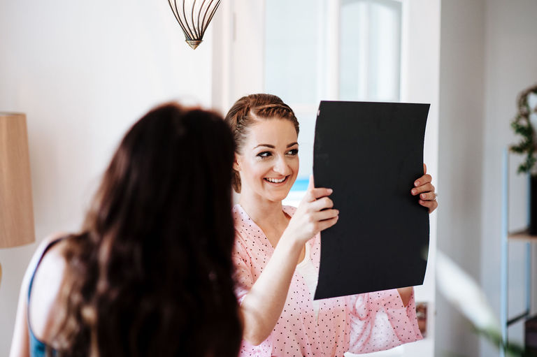 Bride admiring her make up in a mirror