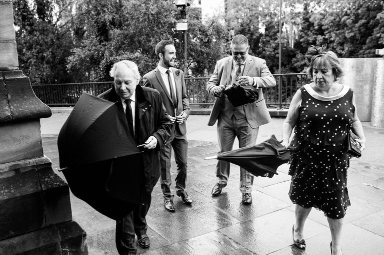 Wedding guests arriving at the church in the rain