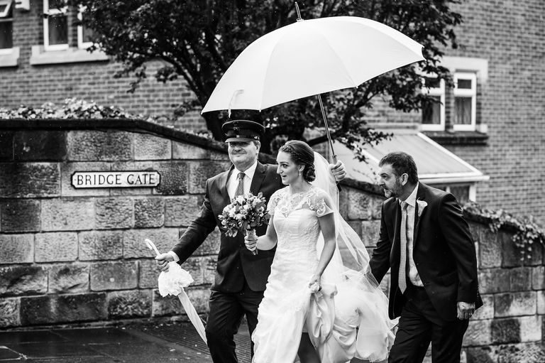 Bride arriving at church under huge umbrella