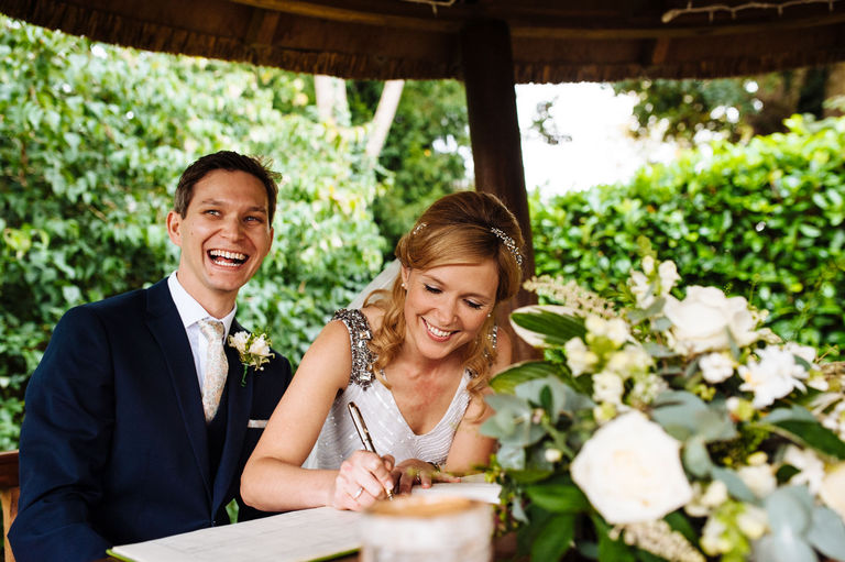 Married couple laughing signing the register
