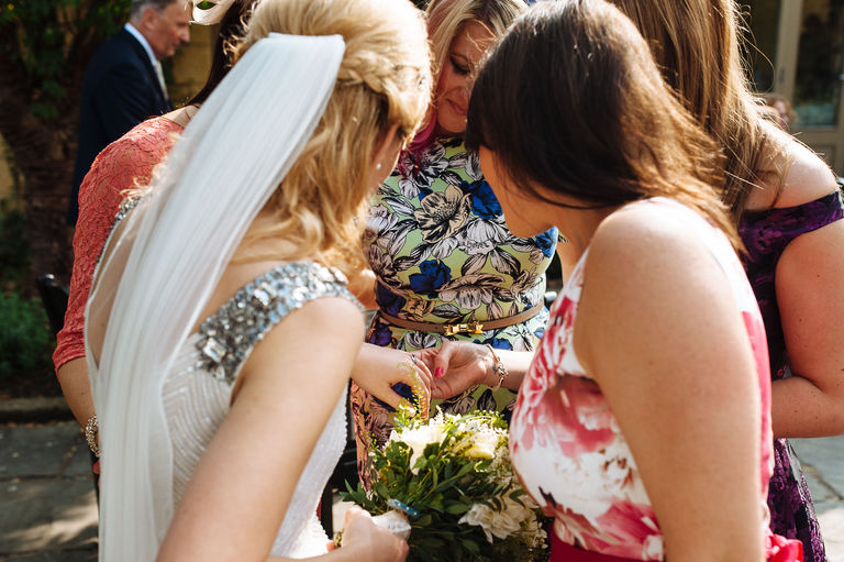 Female guests admire bride's wedding ring