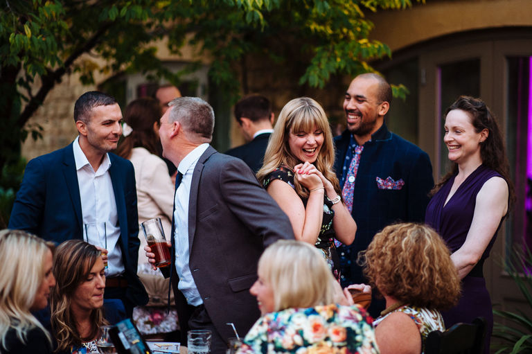 Wedding guests laughing on a summer evening