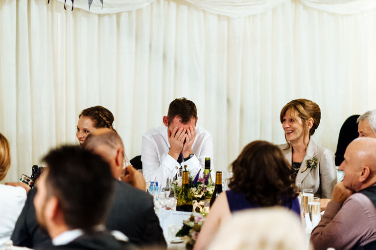 Groom has his head in hands during speeches