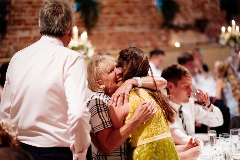 Happy wedding guests hugging