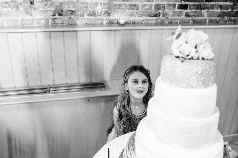 Little girl at a wedding eyes the cake
