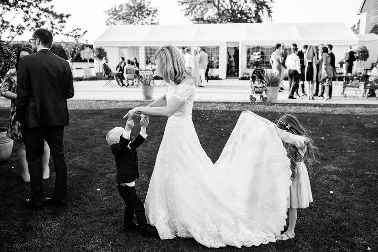 Little girl looks underneath brides dress